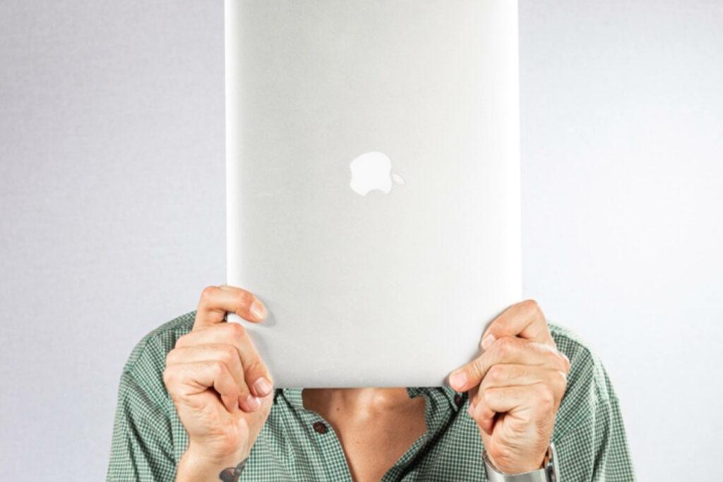 Pim houd een macbook voor zijn hoofd